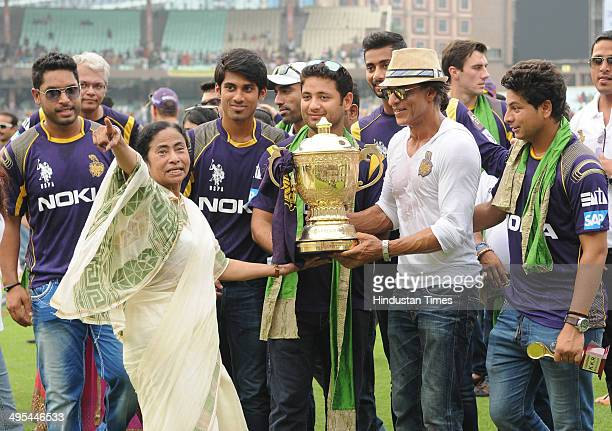 West Bengal Chief Minister Mamata Banerjee with Kolkata Knight Riders owner Shahrukh Khan and players holding the champions trophy during...