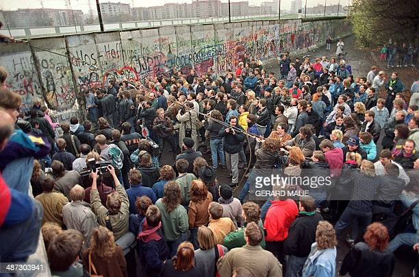 West Berliners crowd in front of the Berlin Wall early 11 November 1989 as they watch people trying to demolish a section of the wall in order to...