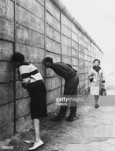 West Berliners peering through the Berlin Wall into the Eastern sector near Check Point Charlie The newly erected wall has no barbed wire only tubes...