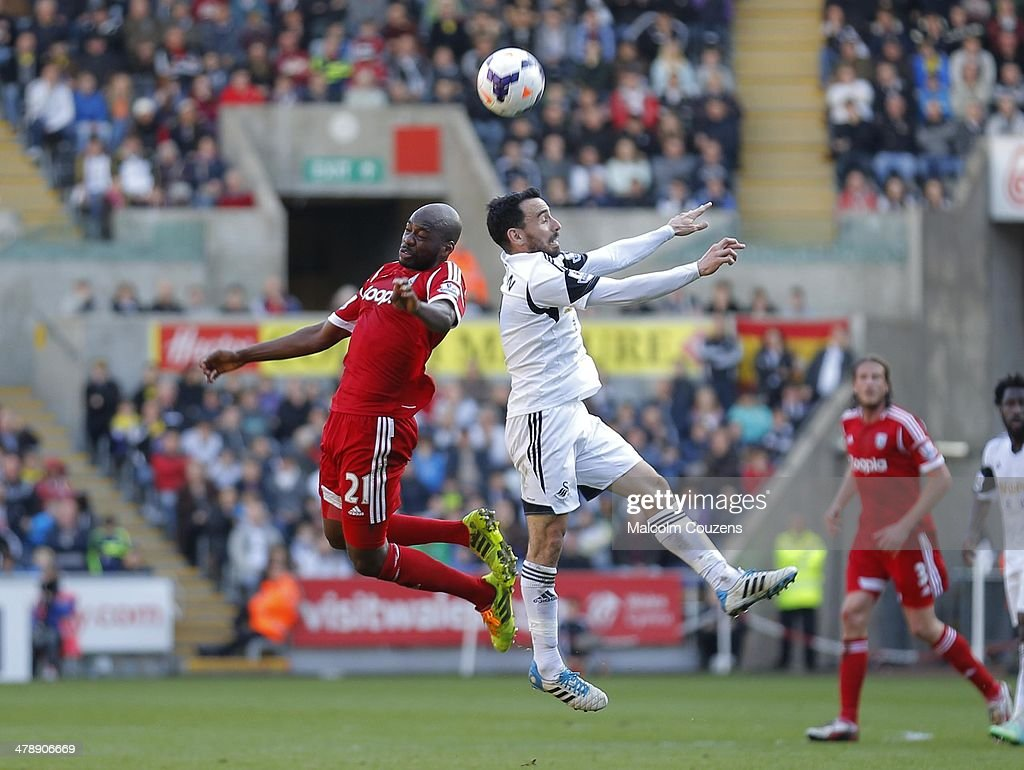 West Bromwich Albion goalscorer Youssouf Mulumbu competes with Leon Britton of Swansea (R) Barclays Premier League match between Swansea City and West Bromwich Albion at The Liberty Stadium on March 15, 2014 in Swansea, Wales.