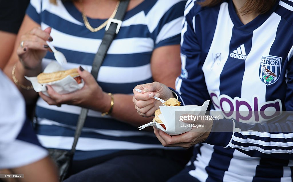 West Bromwich Albion supporters eat a half time meat pie during the Barclays Premier League match between West Bromwich Albion and Swansea City at The Hawthorns on September 01, 2013 in West Bromwich, England.