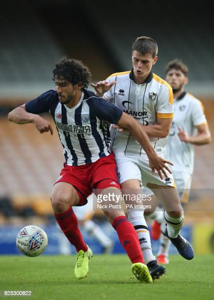 West Bromwich Albion's Ahmed Hegazy holds off challenge from Port Vale's Mike Calverley during the preseason friendly match at Vale Park Stoke