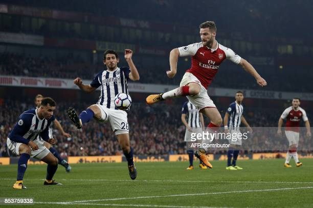 West Bromwich Albion's Egyptian defender Ahmed Hegazy blocks a cross from Arsenal's German defender Shkodran Mustafi during the English Premier...