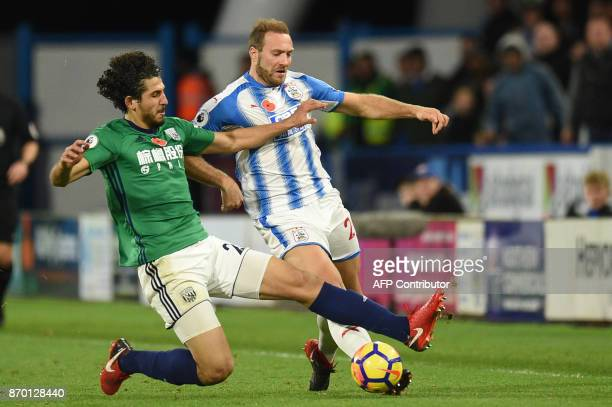 West Bromwich Albion's Egyptian defender Ahmed Hegazy tackles Huddersfield Town's Belgian striker Laurent Depoitre during the English Premier League...