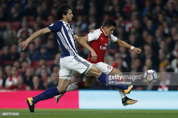 West Bromwich Albion's Egyptian defender Ahmed Hegazy vies with Arsenal's Chilean striker Alexis Sanchez during the English Premier League football...