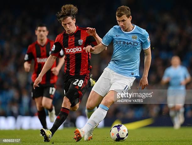 West Bromwich Albion's English defender Billy Jones challenges Manchester City's Bosnian striker Edin Dzeko during the English Premier League...