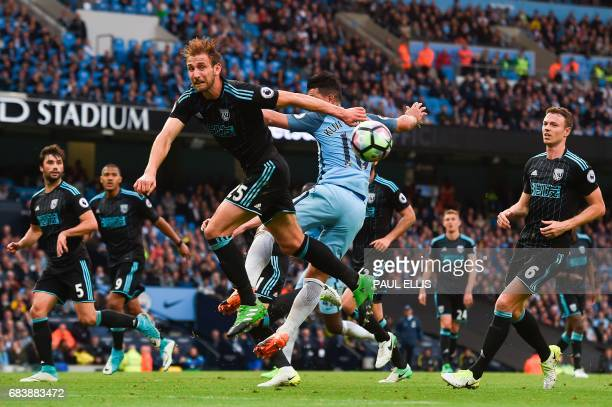 West Bromwich Albion's English defender Craig Dawson defends a cross against Manchester City's Argentinian striker Sergio Aguero during the English...