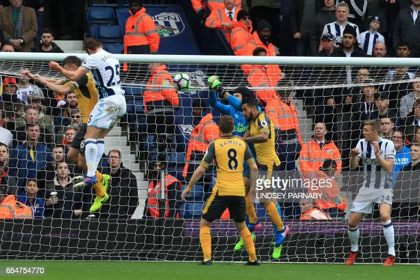 West Bromwich Albion's English defender Craig Dawson heads to score past Arsenal's Czech goalkeeper Petr Cech during the English Premier League...
