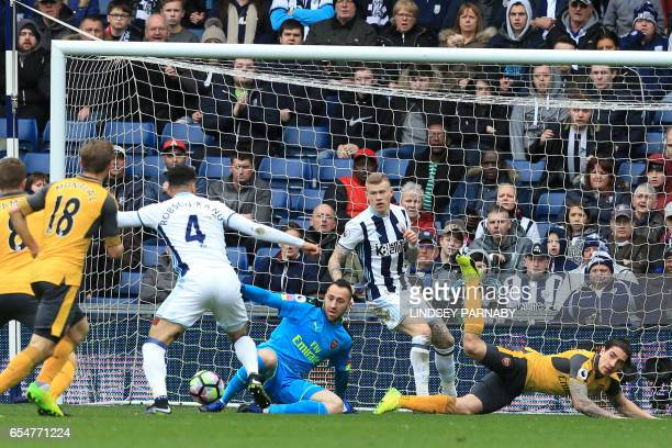 West Bromwich Albion's Englishborn Welsh striker Hal RobsonKanu scores past Arsenal's Colombian goalkeeper David Ospina during the English Premier...