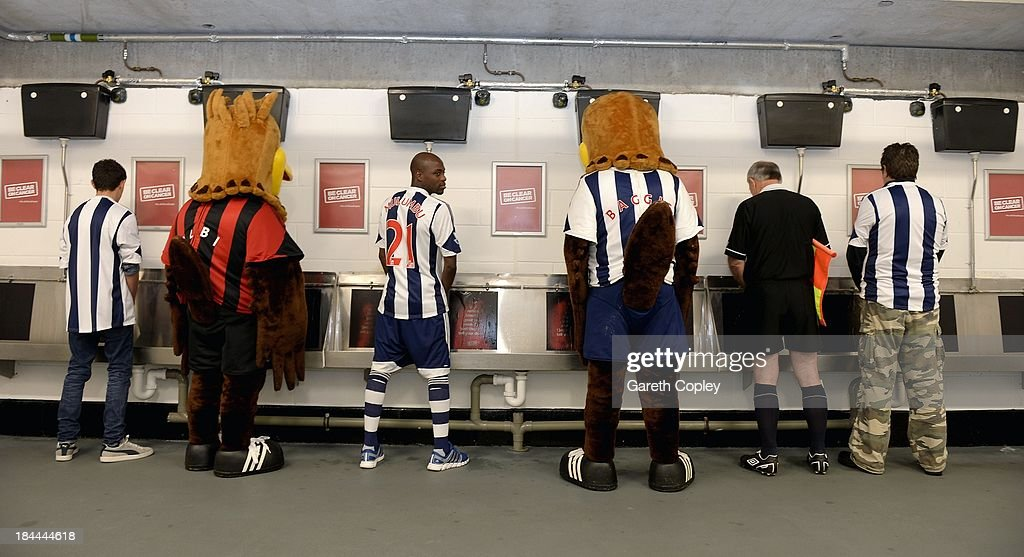 West Bromwich Albion's midfielder, Youssouf Mulumbu, is joined by a linesman, club supporters and mascots to try The Hawthorns heat reactive urinals helping to show bladder and kidney cancer the red card by supporting the new Be Clear on Cancer campaign to raise awareness of blood in pee as a key symptom at The Hawthorns on October 11, 2013 in West Bromwich, England. The club is supporting the new Be Clear on Cancer campaign launching today Tuesday October 15, 2013.
