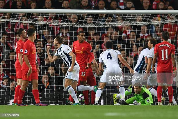 West Bromwich Albion's Northern Irish defender Gareth McAuley turns to celerbate scoring their first goal during the English Premier League football...