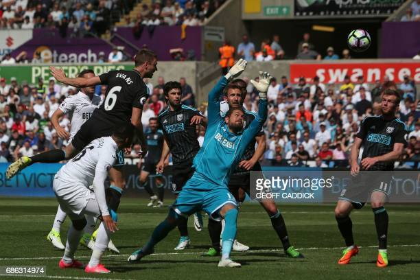 West Bromwich Albion's Northern Irish defender Jonny Evans jumps to head the ball past Swansea City's Swedish goalkeeper Kristoffer Nordfeldt to...