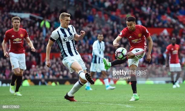 West Bromwich Albion's Scottish midfielder Darren Fletcher defends against Manchester United's English midfielder Jesse Lingard during the English...