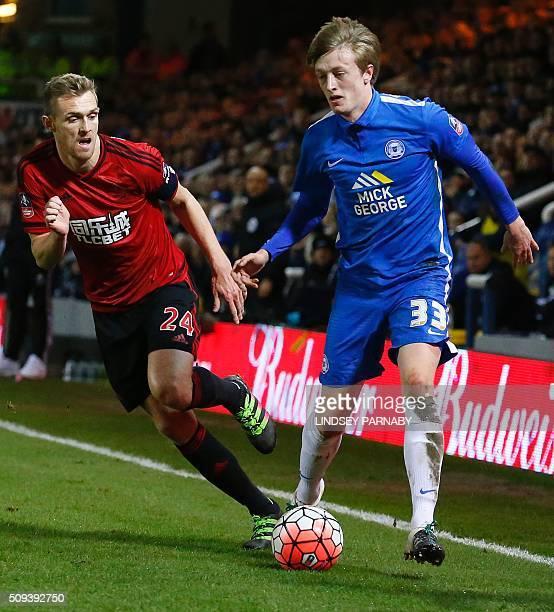 West Bromwich Albion's Scottish midfielder Darren Fletcher vies with Peterborough United's Irish midfielder Chris Forrester during the English FA Cup...