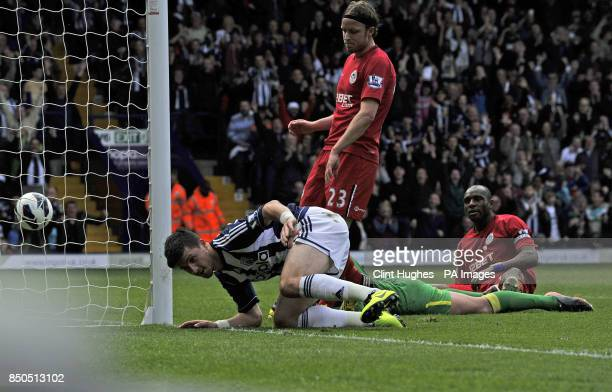 West Bromwich Albion's Shane Long scores the first goal of the game for his side whilst Wigan Athletic's Ronnie Stam and Emmerson Boyce look on...