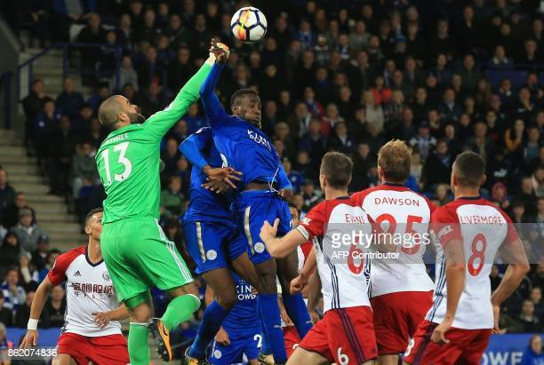 West Bromwich Albion's USborn Welsh goalkeeper Boaz Myhill punches the ball away from the head of Leicester City's Nigerian midfielder Wilfred Ndidi...