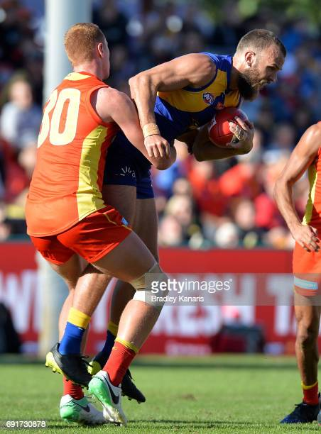 West Coast Eagles player Will Schofield is tackled by Suns player Peter Wright during the round 11 AFL match between the Gold Coast Suns and the West...