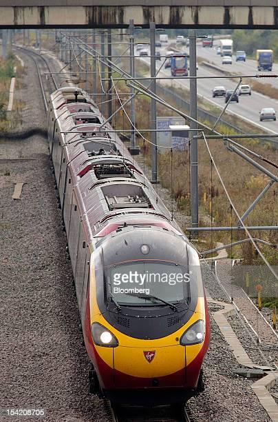 A West Coast train operated by Virgin Trains travels alongside a motorway in Milton Keynes UK on Monday Oct 15 2012 Richard Branson's Virgin Trains...