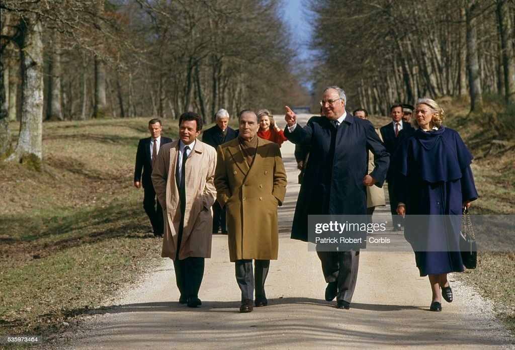 West German chancellor Helmut Kohl and French president Francois Mitterrand go for a walk while meeting in Chambord, France. Joining them is Kohl's wife, Hannelore.