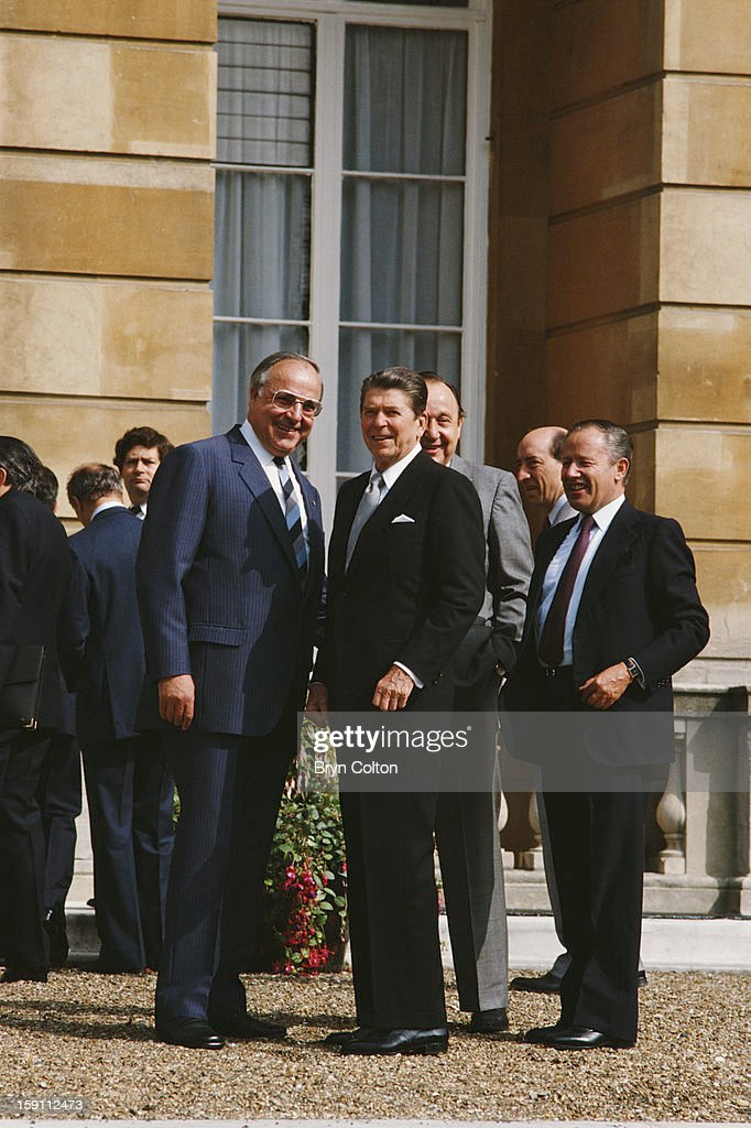 West German Chancellor Helmut Kohl ( left) with US President Ronald Reagan (1911 - 2004) , center, after world leaders posed for a photograph on the steps of Lancaster House as Britain hosted the G7 Seven-Nation Economic Summit in London, 8th June 1984. World leaders gathered in London during June 1984 at the invitation of the Right Honorable Margaret Thatcher, the Prime Minister of the United Kingdom, for the 10th annual economic summit of the G7 group.