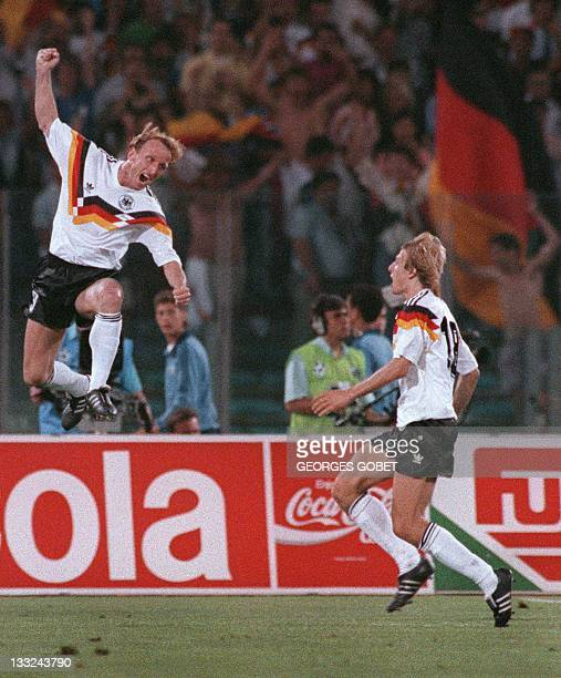 West German defender Andreas Brehme celebrates in front of forward Juergen Klinsmann after scoring the winning goal on a penalty kick during the...