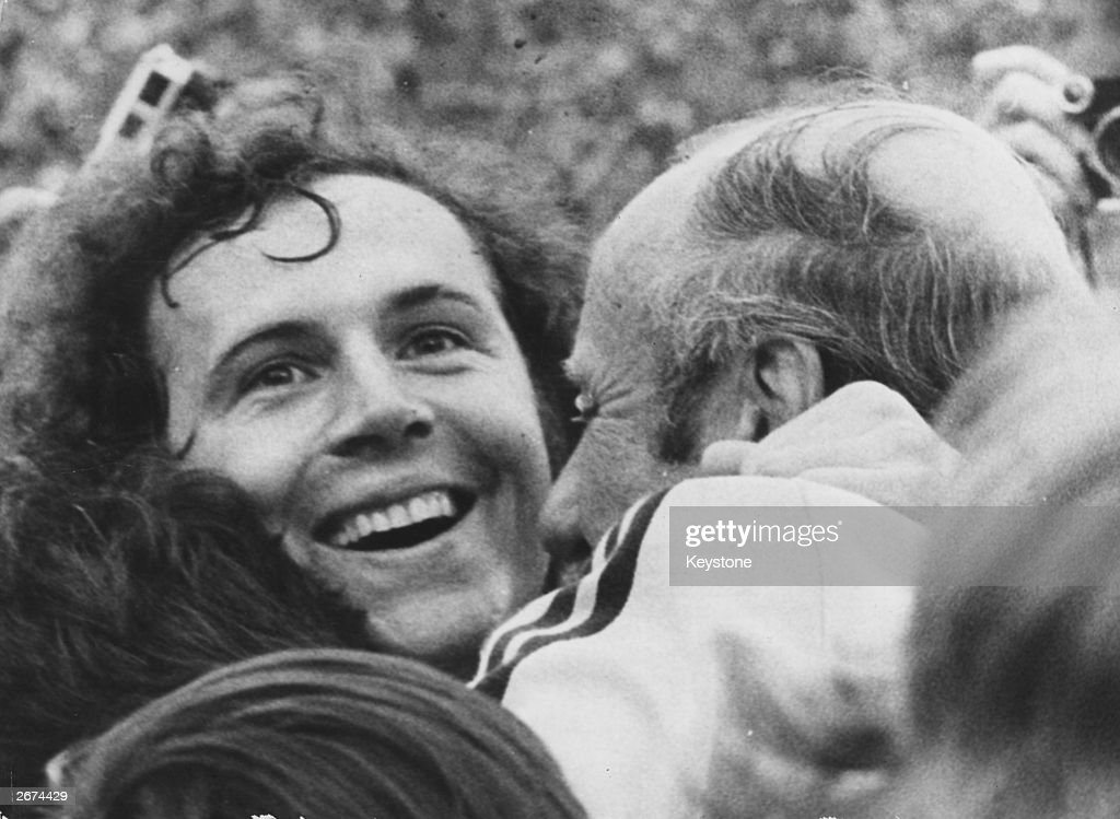 West German footballer <a gi-track='captionPersonalityLinkClicked' href=/galleries/search?phrase=Franz+Beckenbauer&family=editorial&specificpeople=210545 ng-click='$event.stopPropagation()'>Franz Beckenbauer</a> beams with joy as he is embraced by coach Helmut Schon, after his team beat Holland 2-1 to win the 1974 World Cup.