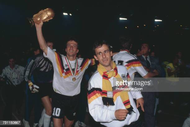 West German footballers Lothar Matthaus behind on left and Pierre Littbarski celebrate with the FIFA World Cup Trophy after West Germany beat...