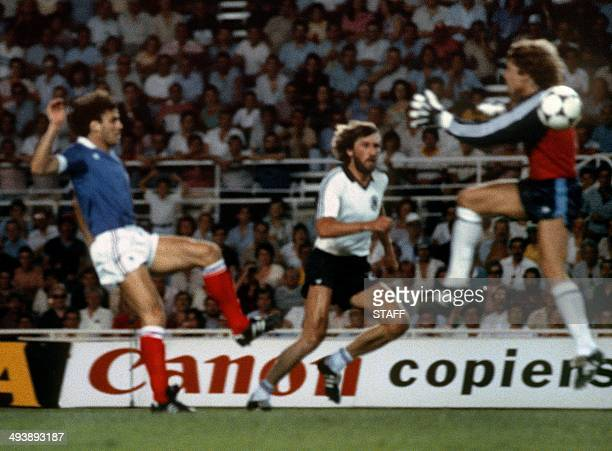 West German goalkeeper Harald Schumacher jumps past the ball as he gets ready to collide with French defender Patrick Battiston during the World Cup...