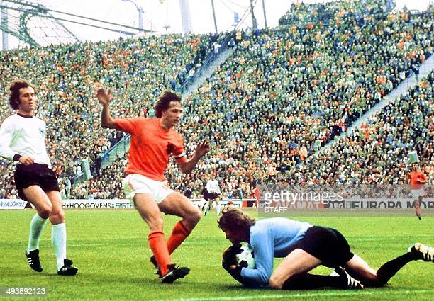 West German goalkeeper Sepp Maier catches the ball in front of Dutch forward Johan Cruyff as defender Franz Beckenbauer looks on 07 July 1974 in...