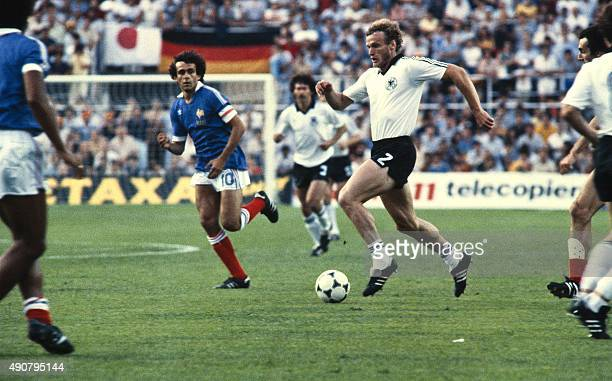West German player runs with ball next to French midfielder Michel Platini during the 1982 World Cup semifinal football match between West Germany...