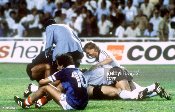 West German players celebrate after forward Horst Hrubesch scored the winning penalty kick in extra time as French midfielder Michel Platini sits on...