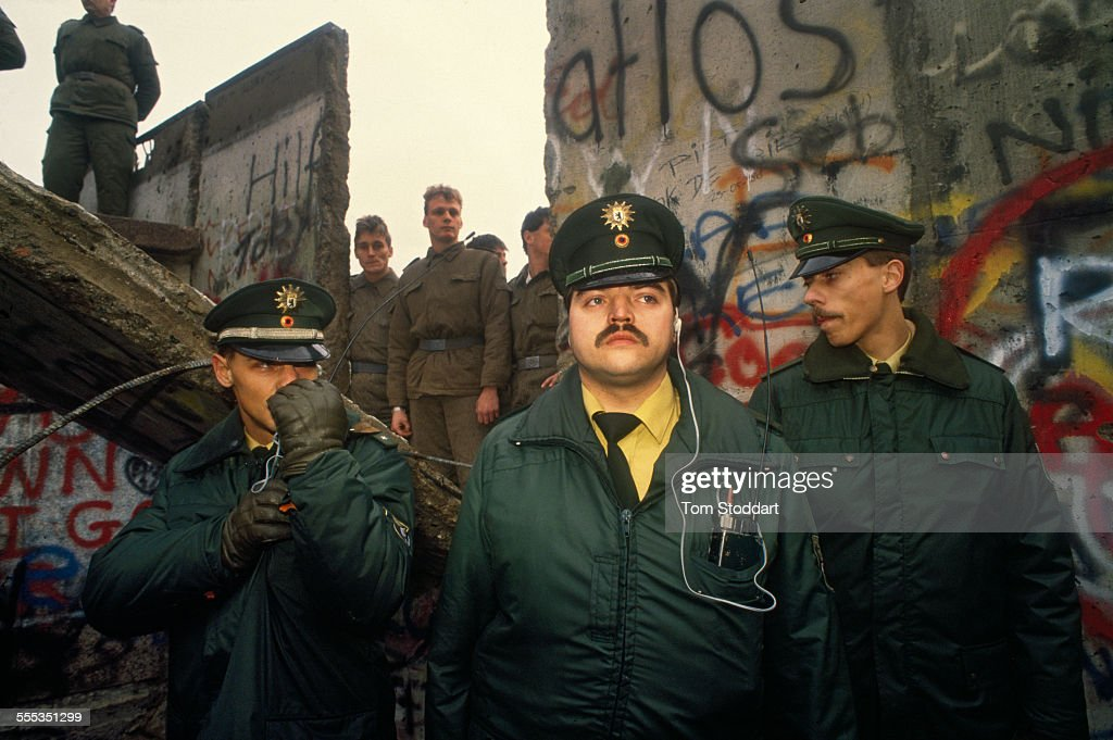 West German police guard the first section of the Berlin Wall to fall, torn down by jubilant crowds near the Brandenburg Gate. In the background East German soldiers stand in the hole that was left when the concrete slab fell forward.