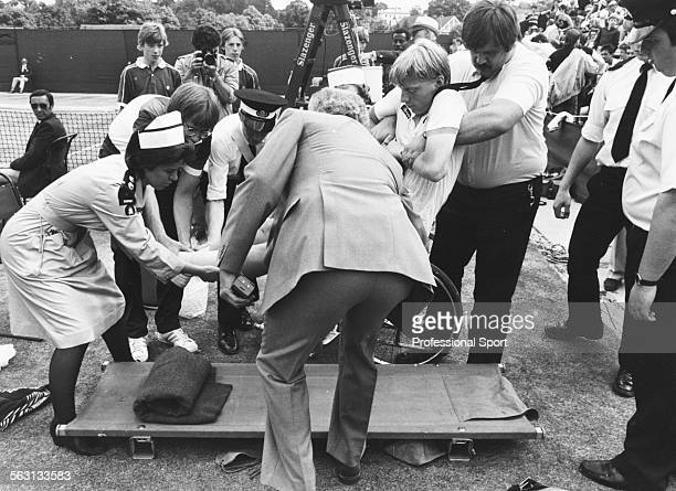 West German tennis player Boris Becker is lifted onto a stretcher after an injury forced him to retire from his third round match against Bill...