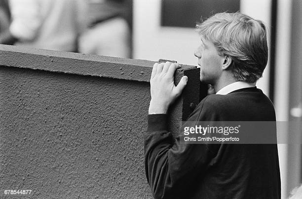 West German tennis player Boris Becker takes a peek to view action in the final of the Ladies' Singles tournament between Martina Navratilova and...