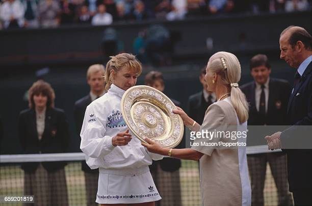 West German tennis player Steffi Graf is presented with the Venus Rosewater Dish trophy by Katharine Duchess of Kent after winning the final of the...