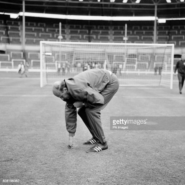 West Germany manager Helmut Schoen inspects a rain soaked Wembley pitch the day before the World Cup final against England