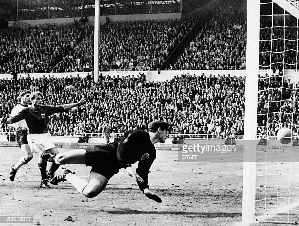 West Germany's goalkeeper Hans Tilkowski watches the ball bounce off the crossbar following a shot by English forward Geoff Hurst as English forward...