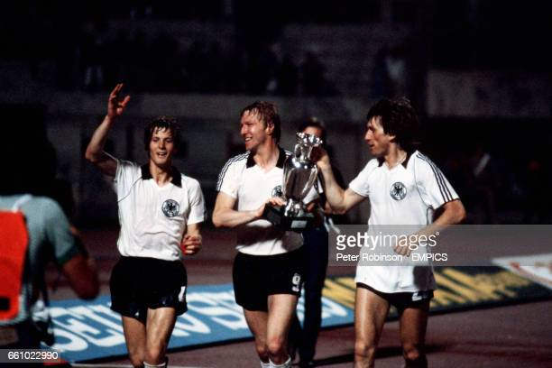 West Germany's KarlHeinz Forster Horst Hrubesch and Manny Kaltz parade the trophy around Rome's Olympic Stadium after their 21 win