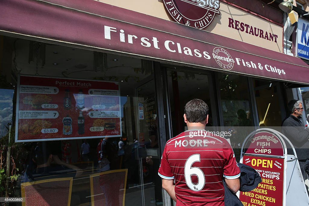 A West Ham fan stands outside a fish and chip shop ahead of the Barclays Premier League match between Crystal Palace and West Ham United at Selhurst Park on August 23, 2014 in London, England.