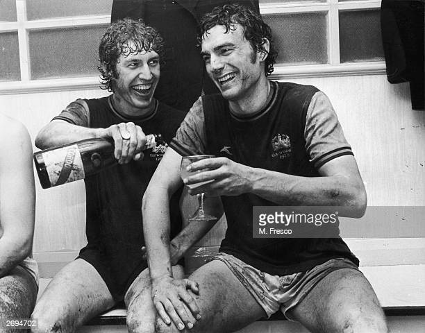 West Ham footballers Pat Holland and Trevor Brooking sharing a glass of champagne after Brooking had scored twice against Eintracht Frankfurt in the...