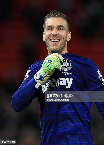 West Ham goalkeeper Adrian grabs the badge on his shirt as he celebrates the draw following the Barclays Premier League match between Manchester...