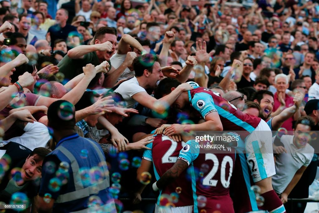 TOPSHOT - West Ham players and fans celebrate the opening goal scored by West Ham United's Senegalese midfielder Cheikhou Kouyate during the English Premier League football match between West Ham United and Swansea City at The London Stadium, in east London on April 8, 2017. / AFP PHOTO / Ian KINGTON / RESTRICTED TO EDITORIAL USE. No use with unauthorized audio, video, data, fixture lists, club/league logos or 'live' services. Online in-match use limited to 75 images, no video emulation. No use in betting, games or single club/league/player publications. /