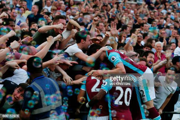 TOPSHOT West Ham players and fans celebrate the opening goal scored by West Ham United's Senegalese midfielder Cheikhou Kouyate during the English...