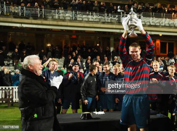 West Ham United Chairman David Gold looks on as Royal Engineers AFC Captain Jay Hubbard lifts the first ever FA Cup Trophy after winning the First FA...