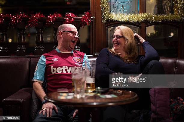 West Ham United Football Club fan Darren Powers laughs with Debbi Doughty as they drink at the Boleyn Pub in Upton Park on December 3 2016 in London...