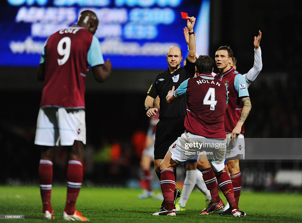 West Ham United players react as match referee Anthony Taylor sends off <a gi-track='captionPersonalityLinkClicked' href=/galleries/search?phrase=Carlton+Cole&family=editorial&specificpeople=215313 ng-click='$event.stopPropagation()'>Carlton Cole</a> of West Ham United for a high tackle during the Barclays Premier League match between West Ham United and Everton at the Boleyn Ground on December 22, 2012 in London, England.