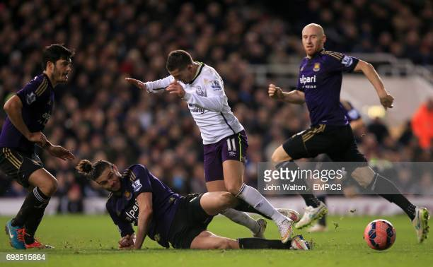 West Ham United's Andy Carroll slides in on Everton's Kevin Mirallas