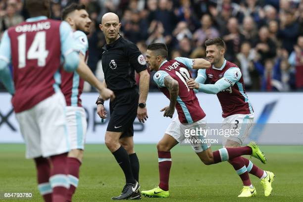 West Ham United's Argentinian midfielder Manuel Lanzini celebrates with West Ham United's English defender Aaron Cresswell after scoring from a free...