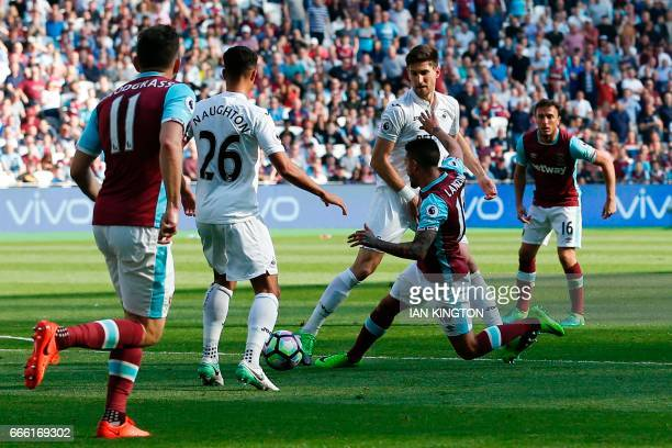 West Ham United's Argentinian midfielder Manuel Lanzini goes down in the penalty area and gets a yellow card apparently for simulation during the...