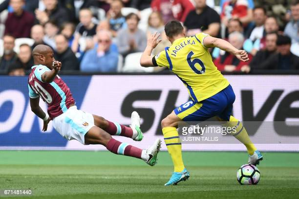 West Ham United's Argentinian midfielder Manuel Lanzini vies with Everton's English defender Phil Jagielka during the English Premier League football...